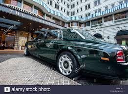 rolls royce car parked outside an oxfam charity shop in chelsea