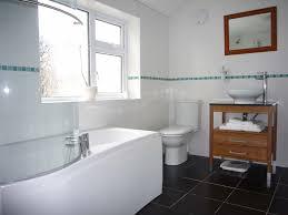 bathroom towel storage dark ceramic tile white tub bathroom