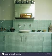 glass fronted cabinet above basin in pastel green mosaic tiled