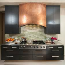 a gorgeous copper tile range hood stands out against sleek black