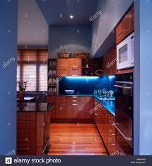 lighting above blue tiled splash back in modern blue kitchen with