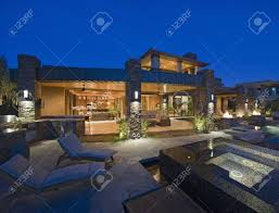 House Patio by House Exterior Lit Up At Night With Patio Furniture Stock Photo
