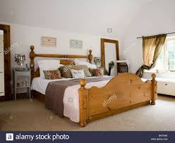 large pine bed with white bedlinen and brown throw in country