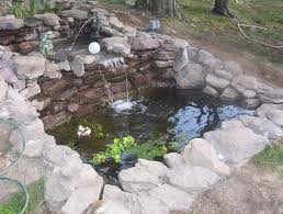 dashing pond with stone material and beautiful flower garden idea