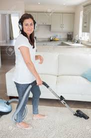 Cleaning The House by Woman Cleaning The House While Wearing Headphones Stock Photo