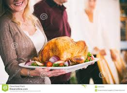 family traditions for thanksgiving thanksgiving woman holding platter with roast turkey and garnis