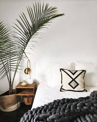 Minimalistic Bedroom Large Plant White Walls Gold Lamp White Sheets Large Knit Grey