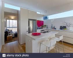 modern open plan kitchen stools at breakfast bar in modern open plan kitchen and living