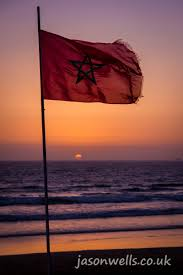 Uk Beach Flags The African Sun Sets Behind A Moroccan Flag On The Coast Of