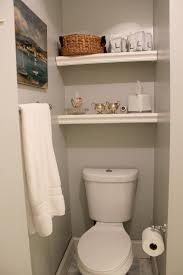 bathroom tidy ideas floating white shelves on the cream wall above white toilet of