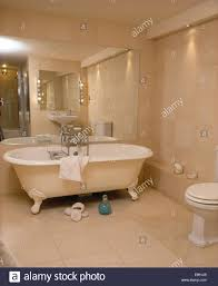 modern roll top bath in modern bathroom with slate flooring and