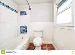 white interior of bathroom with mosaic blue tile wall trim stock