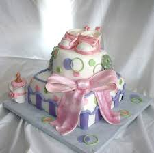 whimsical baby shower cake in pink green and purple with edible