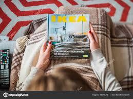 woman reading ikea catalog cover before furnishing house u2013 stock