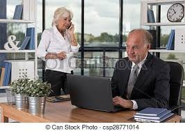 picture of busy aged pair working in bureau stock photography