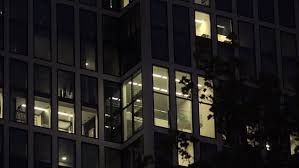 office building at with window lights on 4k large black