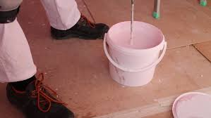 mixing paint in a bucket with a brush bright pink color slow