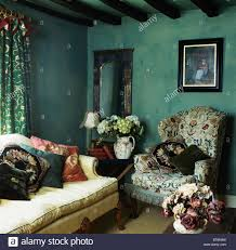 picture on wall above patterned wing chair in dark green cottage