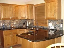 backsplash tile with black granite countertops honey oak kitchen