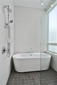 Grey Wall Bathroom White Porcelain Freestanding Tub Placed On Grey Tiled Flooring In