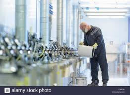 worker mixing paint in automotive parts spray paint factory stock