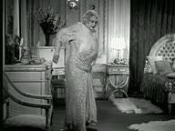 1937 bw ws woman in evening dress beginning to undress in front of
