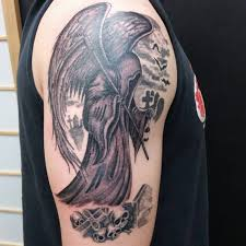 grey ink winged grim reaper tattoo on man right shoulder