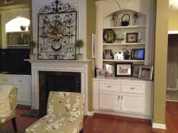 white concrete fireplace with mantle shelf also cupboard with book