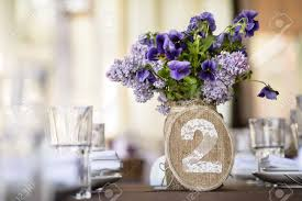 wedding table decor with syringa and pansy flowers table number