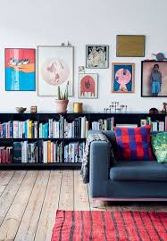 Colorful Artwork In A Gallery Wall Above Black Bookshelves In A - Living room design photos gallery