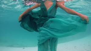 underwater young beautiful in dress posing submerged under