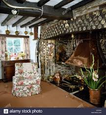 cottage living room with floral print armchair beside inglenook