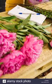 pink flowers on table beside order pad in flower shop close up