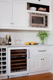 wine rack cabinet over refrigerator kitchen pantry features white shaker cabinets fitted with a wine