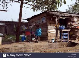she shack nigerian lady sits in the shade outside a roadside shack where she