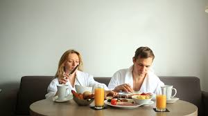 young couple man and woman having breakfast on sofa in hotel room