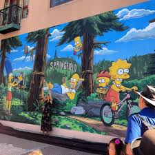 welcome home bart lisa marge maggie and homer yeardley smith the voice of lisa simpson helps dedicate the simpsons mural at