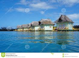 tropical resort with thatched overwater bungalow stock photo