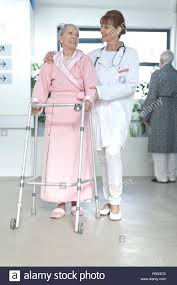 doctor leading elderly patient with walking frame on hospital