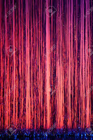 a stage curtain of pink purple and blue with streamers provides