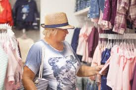 elderly woman clothes elderly woman choosing baby clothes in the shop stock photo
