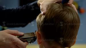 hairdresser cut hair behind ear of the boy with a haircut machine