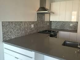 marble mosaic herringbone pattern with schluter trim backsplash