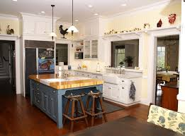 blue kitchen cabinets and yellow walls looking butcher block kitchen island in kitchen