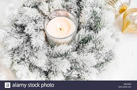 white snowy christmas wreath with burning candle ribbon and