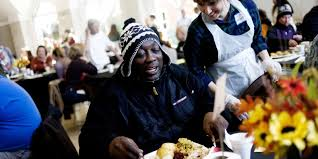 volunteers serve thanksgiving meals for the needy at karm