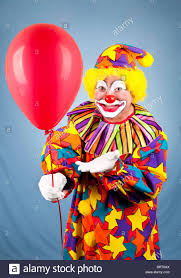 clown balloon happy birthday clown holding out a balloon for you stock photo