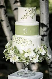 this white wedding cake with green floral designs is a beautiful