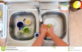 l evier de cuisine personne de cuvette de vaisselle nettoyant l évier de cuisine photo