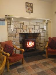 white stone fireplace with white wooden mantel shelf and black